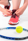 Woman tying lace near racket for tennis on a white Stock Images