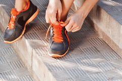Woman tying laces of running shoes before training sitting on stairs Stock Photo