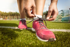 Woman tying laces on sneakers on grass field Stock Images