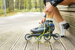 Woman tying roller skates. Woman tying her roller skates stock photography