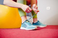 Woman tying shoe at gym, sitting on a fitness ball. Woman tying shoe at gym, sitting on a yellow fitness ball stock photography