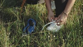 Woman tying shoe laces in the field, nature walk,close-up,slow motion.