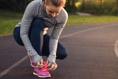 Woman tying shoe laces. Runner in the summer park.  Stock Photo