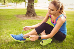 Woman tying shoelace at park Royalty Free Stock Photo