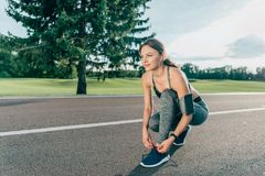 Woman tying shoelaces. Caucasian woman in sportswear tying shoelaces before jogging Stock Images