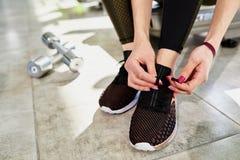 Woman tying shoelaces. Closeup portrait of a woman tying shoelaces Stock Photo