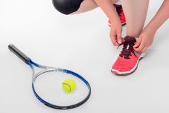 Woman tying shoelaces before a game of tennis Royalty Free Stock Images