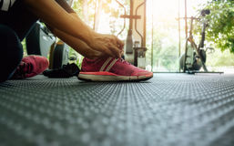 Woman tying shoelaces at gym Royalty Free Stock Photos