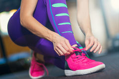 Woman tying shoelaces. Pink sneakers. Purple tights Royalty Free Stock Image