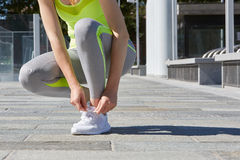Woman tying shoelaces before running outdoor, sunlight Royalty Free Stock Images