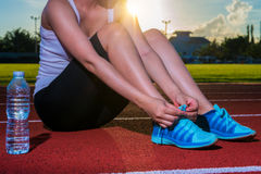 Woman tying shoelaces on running racetrack, red rubber racetrack. S in outdoor stadium. Closeup of female sport fitness runner getting ready for jogging Royalty Free Stock Photos