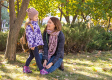 Woman tying shoelaces young daughter. Royalty Free Stock Image