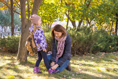 Woman tying shoelaces young daughter. Stock Photos