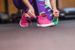 Woman tying shoelaces stock photography