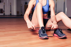 Woman tying shoes in the gym Royalty Free Stock Images