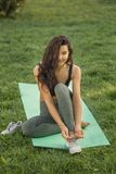 Woman tying shoes. Healthy lifestyle concept. Happy Sport Life. Pretty young woman sitting on yoga mat outdoors and tying shoelaces on sneakers and looking at stock photography