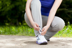Woman tying shoes Stock Image