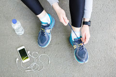 Woman tying shoes laces before running top view Stock Photos