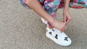 Woman tying shoes while running stock footage