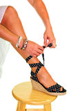 Woman tying the straps to hod her shoes on Stock Photo