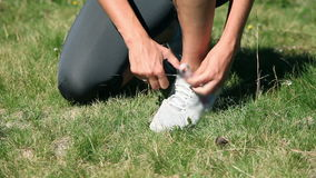 Woman tying up her shoelaces while running stock footage