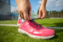 Woman tying up pink sneakers on soccer field Stock Photos