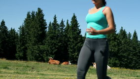 Woman is tying up shoelaces while running in nature stock video footage