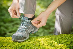 Woman Tying Walking Shoe Over Moss Royalty Free Stock Photo