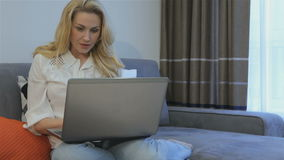 Woman types on laptop at home
