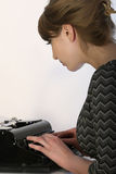 Woman with typewriter. Business woman typing on vintage typewriter, shot in studio Stock Photo