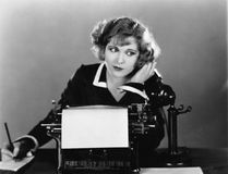 Woman at typewriter on telephone royalty free stock photo