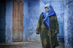 A woman in typical moroccan clothing, blue Medina of Chefchaouen. A woman in typical moroccan clothing, walking down a street in the blue Medina of Chefchaouen Royalty Free Stock Photo