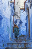 A woman in typical moroccan clothing, blue Medina of Chefchaouen. A woman in typical moroccan clothing, walking down a street in the blue Medina of Chefchaouen Royalty Free Stock Images