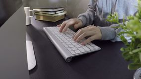 Woman typing on computer in office stock video