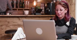 Woman typing on computer. In vintage and stylish coffee shop or restaurant stock footage