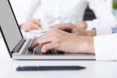 Woman is typing while her colleague in the background is writing Royalty Free Stock Photo