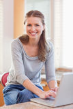 Woman typing on her laptop in the kitchen Royalty Free Stock Images