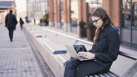 Woman typing on her laptop in the street. Young beautiful woman is typing on her laptop keyboard sitting on a bench in the street. Locked down real time medium stock footage
