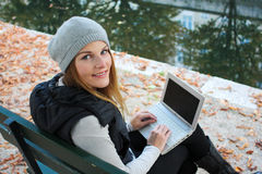 Woman typing on her netbook. Woman sitting on a bench with her Laptop Stock Image