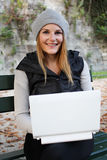 Woman typing on her netbook and smiling. Woman sitting on a bench with her Laptop Royalty Free Stock Images
