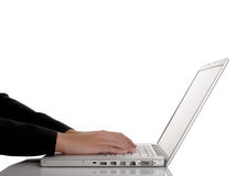Woman typing on isolated laptop. Isolated image of a woman typing on a modern laptop computer Stock Photo