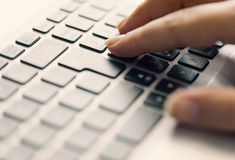 Woman typing on keypad Stock Photos