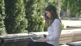 Young woman typing on laptop computer keyboard while sitting on the bench on the street. Woman typing on laptop computer keyboard while sitting on the bench on stock footage