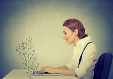 Woman typing on laptop computer with screen made of alphabet letters flying up Stock Images