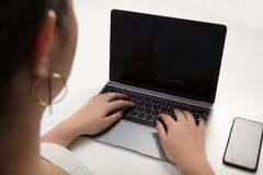 Woman typing on a laptop computer. Viewed from behind over the shoulder with focus to the blank black screen Stock Photo