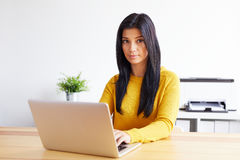 Woman typing on laptop in home office Stock Photography