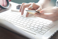 Woman typing on laptop keyboard and holding credit card Royalty Free Stock Photography
