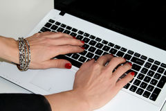 Woman typing on the laptop. Manicured hands typing on the laptop stock photography