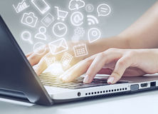Woman typing on laptop and media icons fly off Stock Image