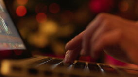 Woman Typing in Laptop in New Year Eve. Closeup shot of woman fingers typing on laptop keypad. Sparkling fairy lights on Christmas tree on the background stock video